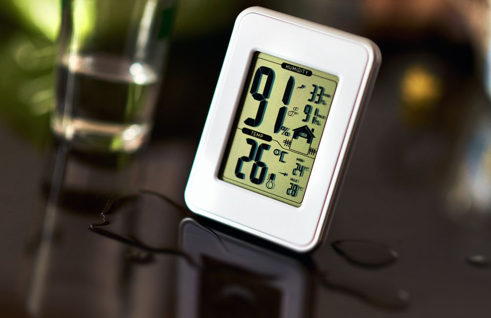 Digital display of electronic hygrometer sitting on a table.