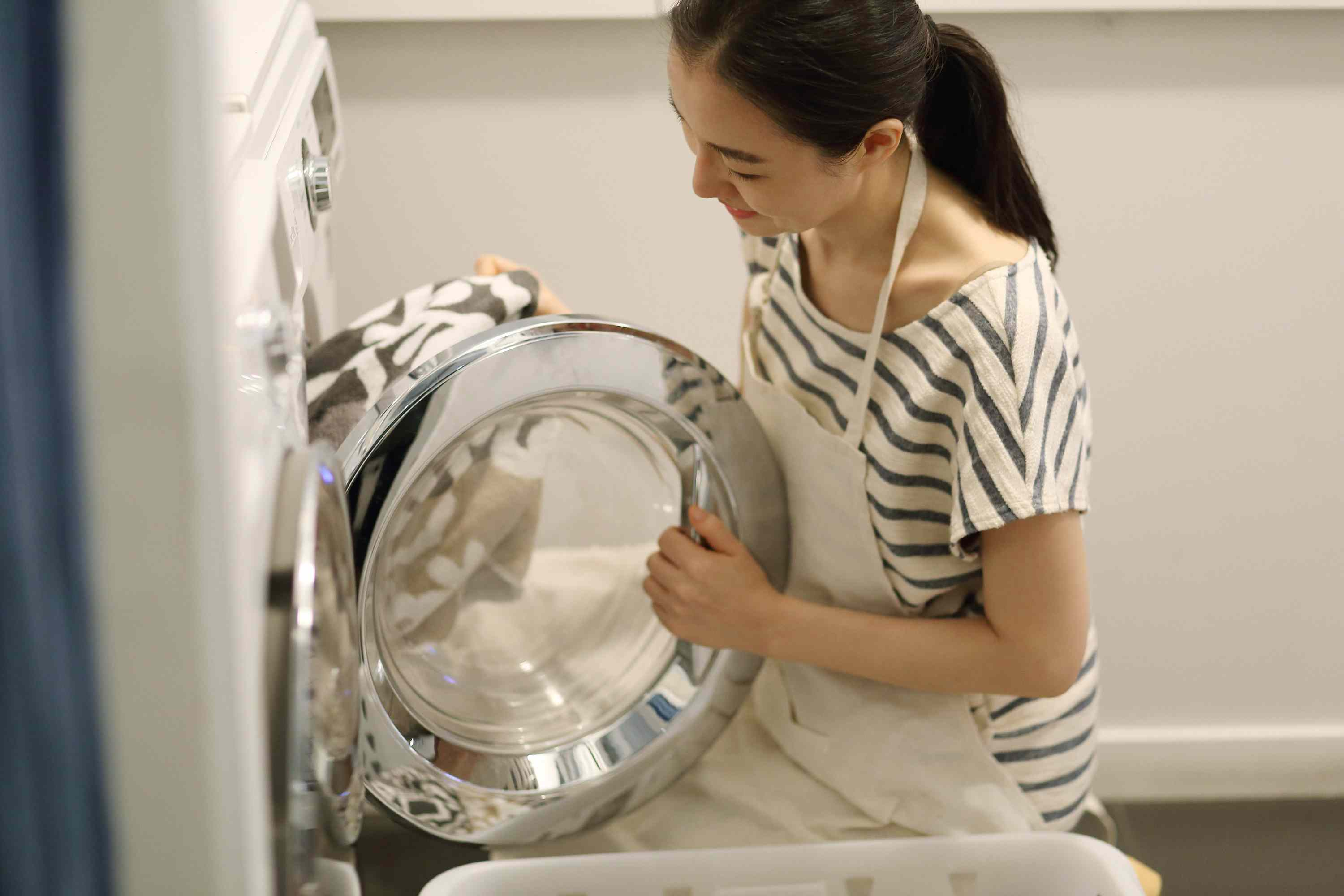 Woman loading clothes into a washer.