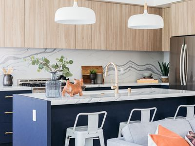 Kitchen with navy blue lower cabinets, light wood upper cabinets and white marble-top island in middle