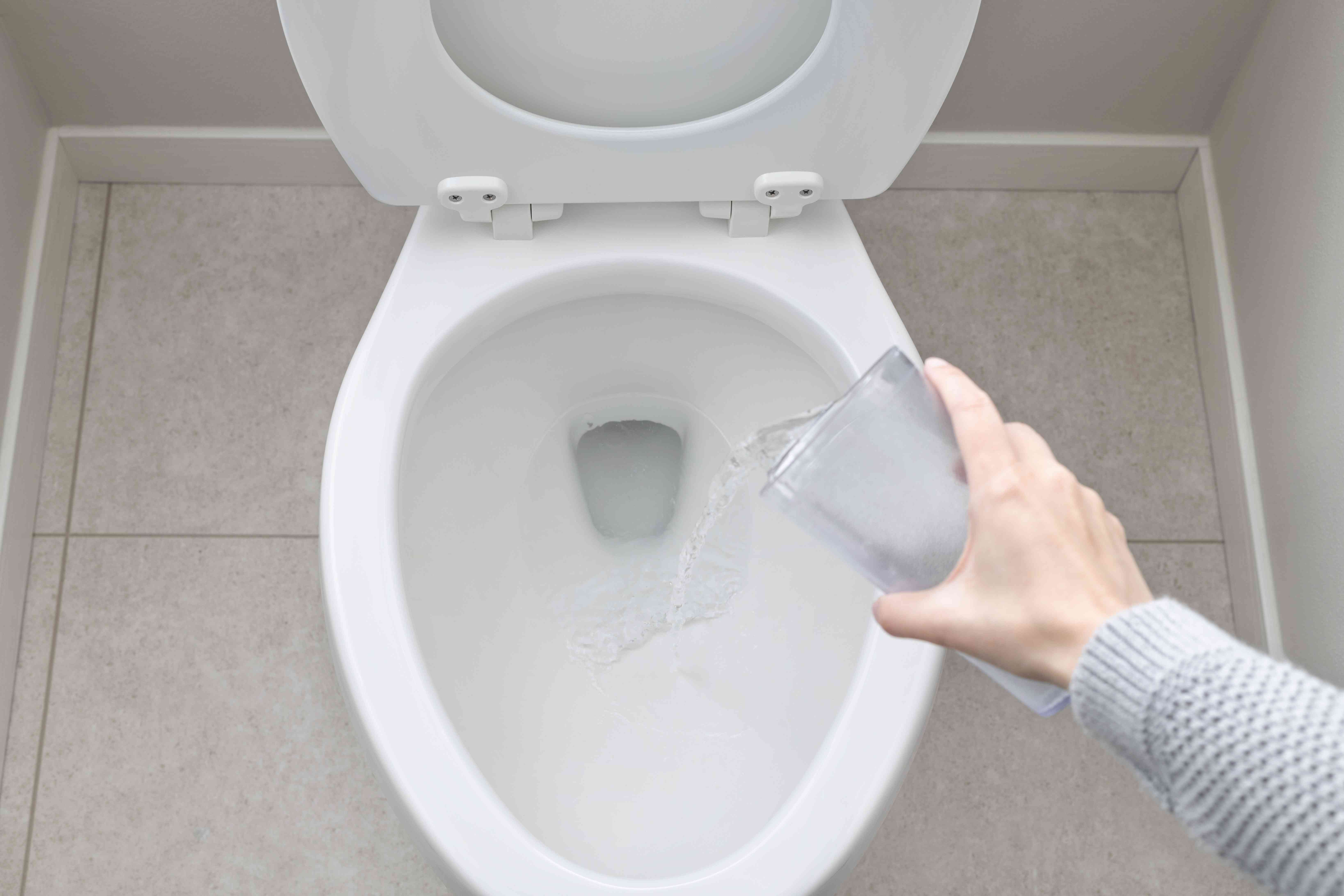 Toilet bowl being filled with water from cup held in hand