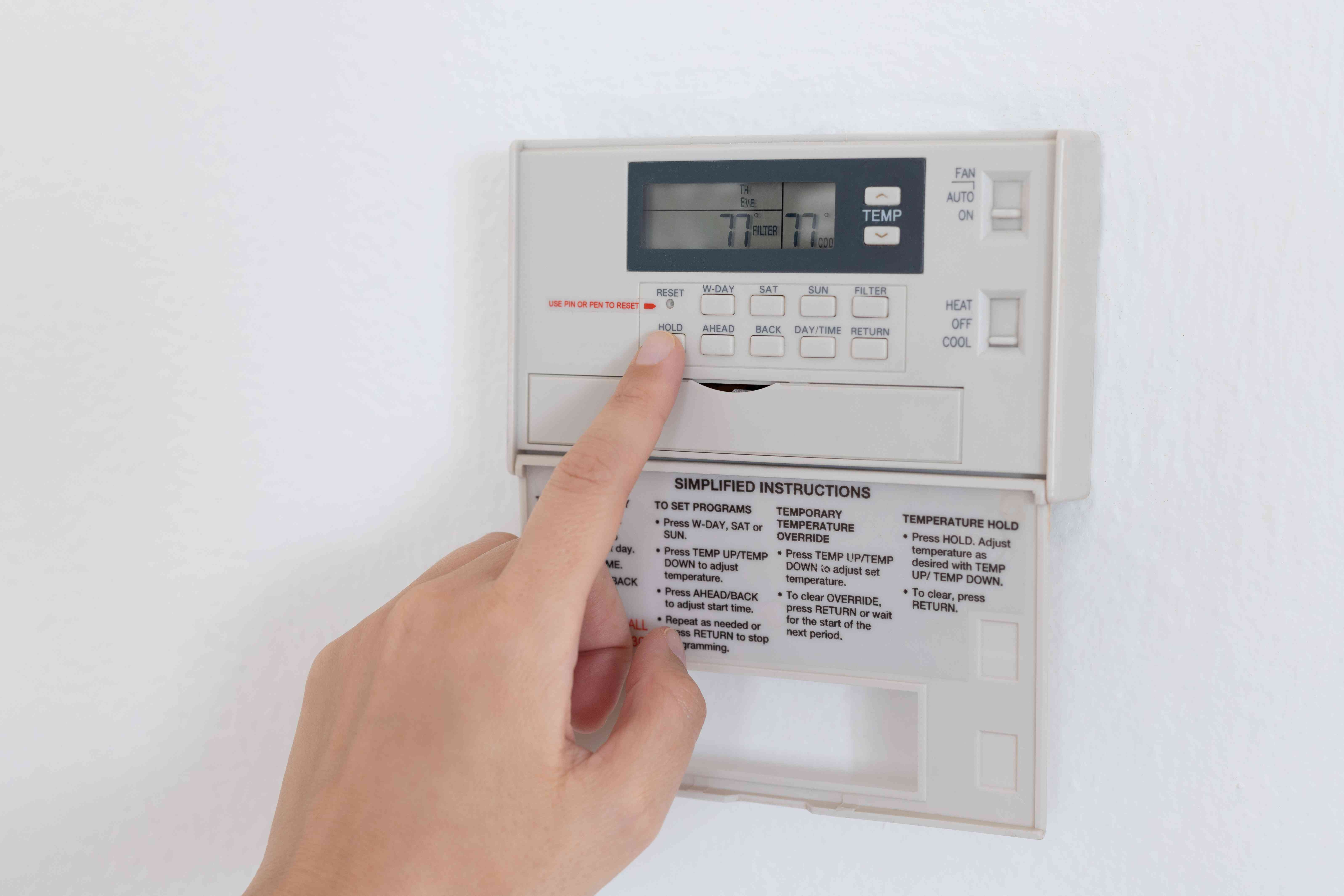 Programmable thermostat being adjusted to lower electric bill