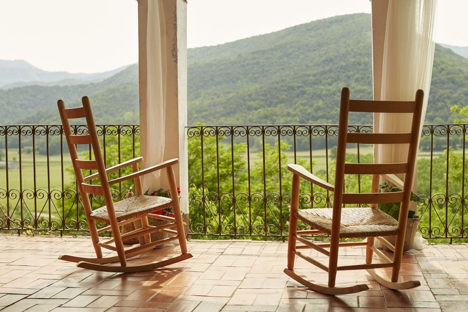 Empty rocking chairs in balcony against mountains
