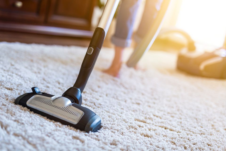 Woman using a vacuum cleaner while cleaning carpet in the house.