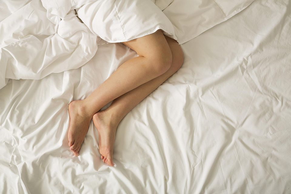 Directly above view of bare female legs in bed