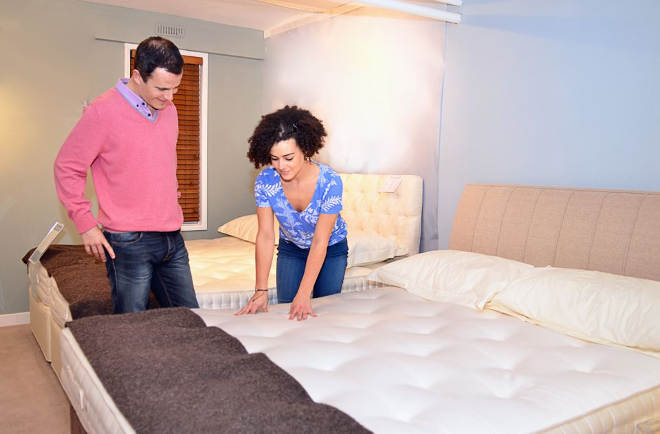 Couple testing beds in furniture shop showroom