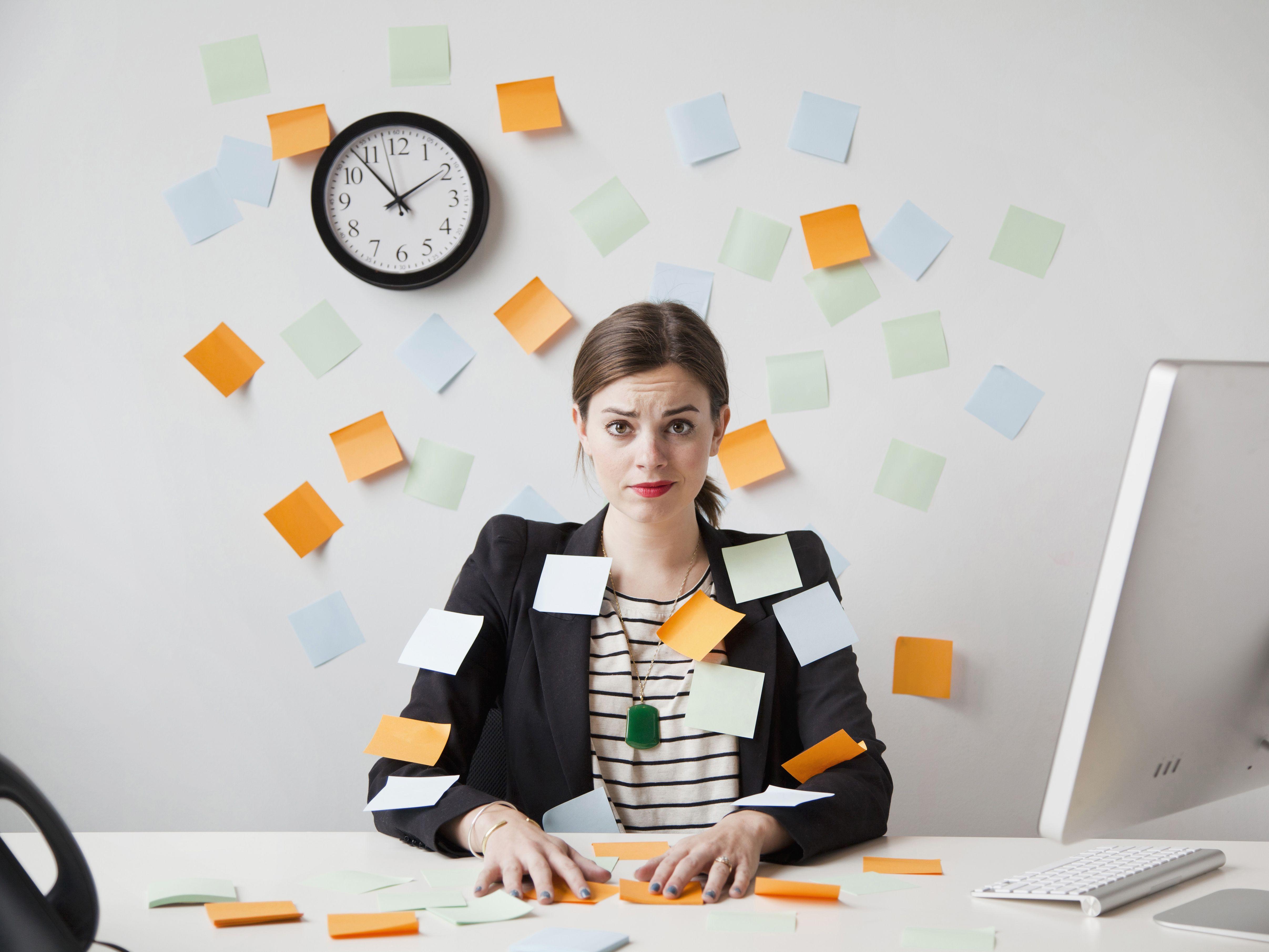 Foto de estudio de una mujer joven que trabaja en la oficina cubierta con notas adhesivas