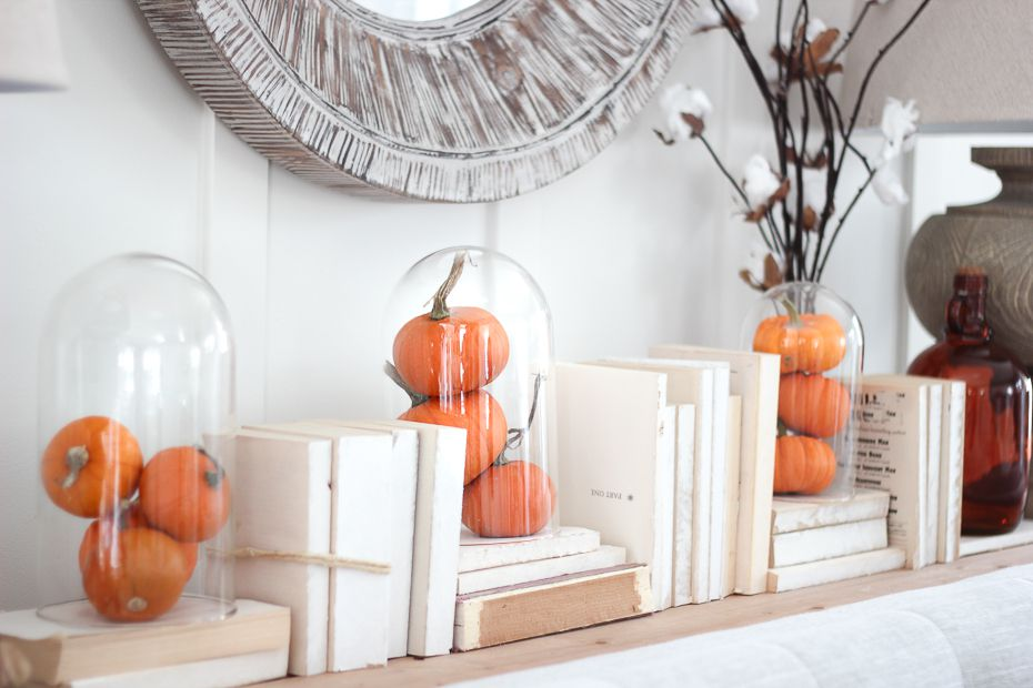 Mini pumpkins under a glass cloche.