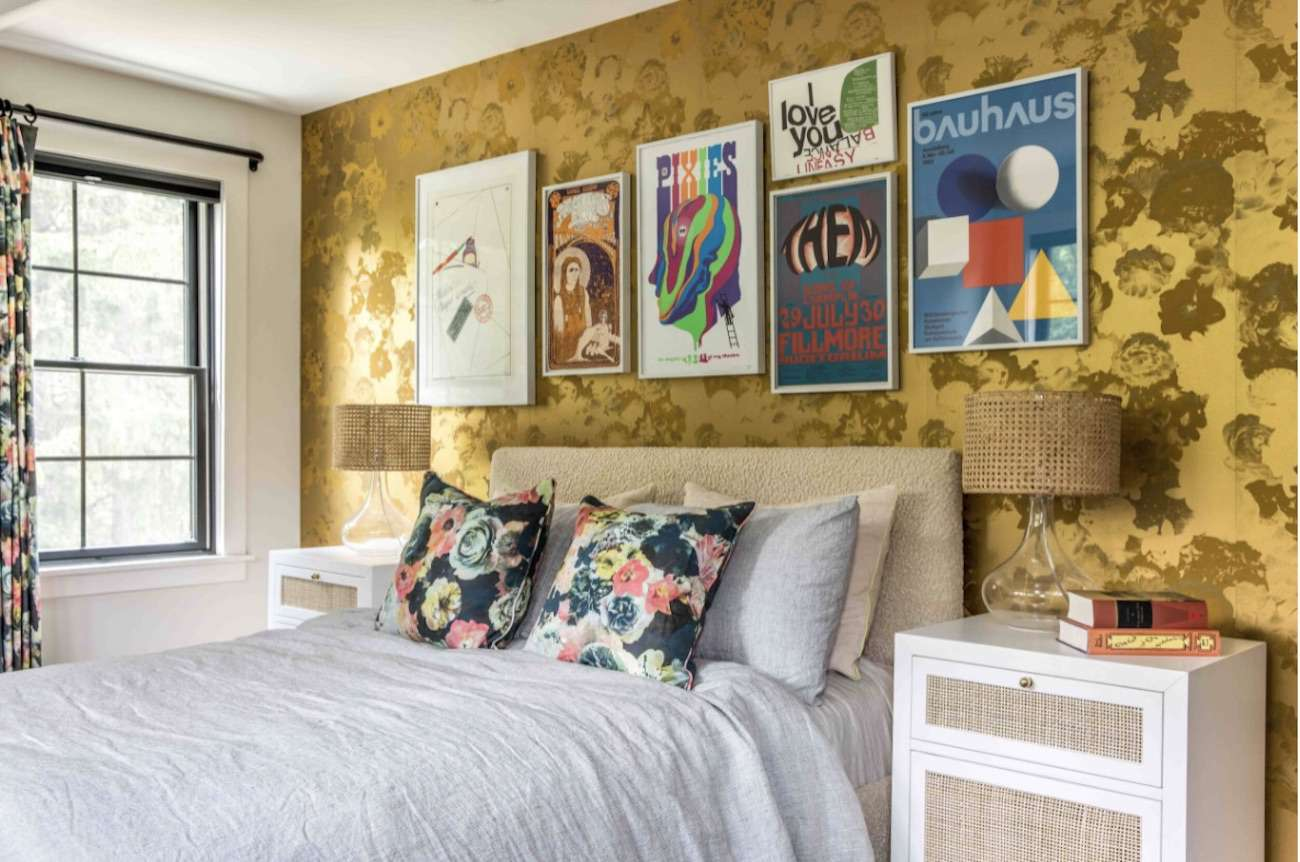 bedroom with yellow floral foil accent wall, framed prints hanging above bed, floral pillows and curtains