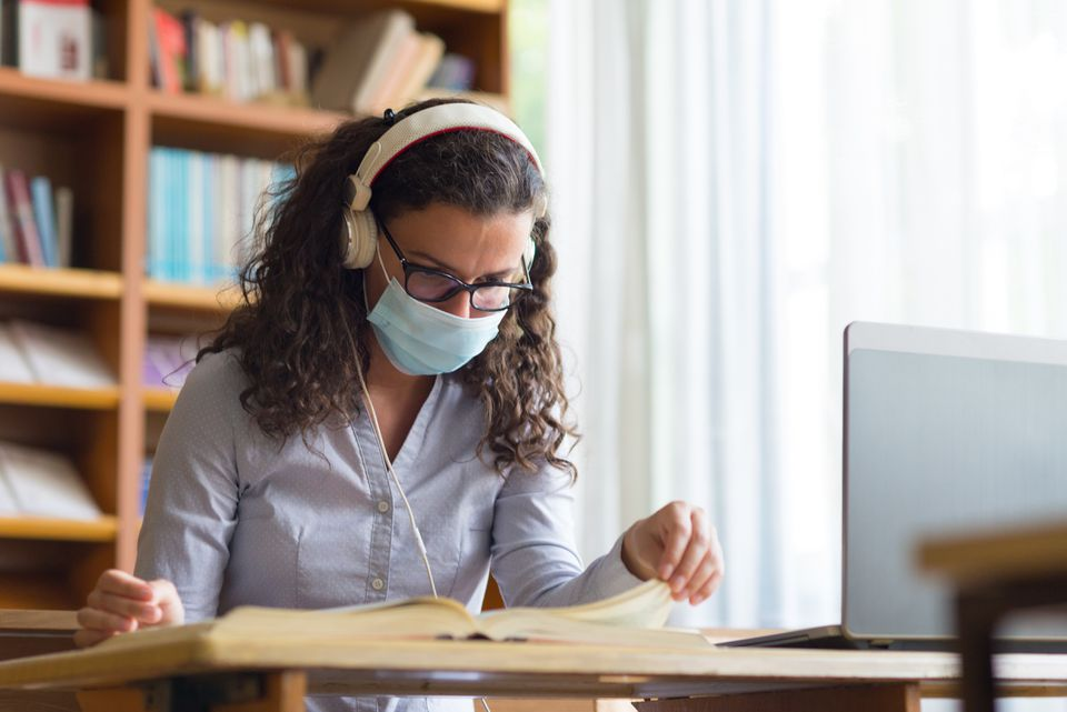 Woman wearing mask while studying in library