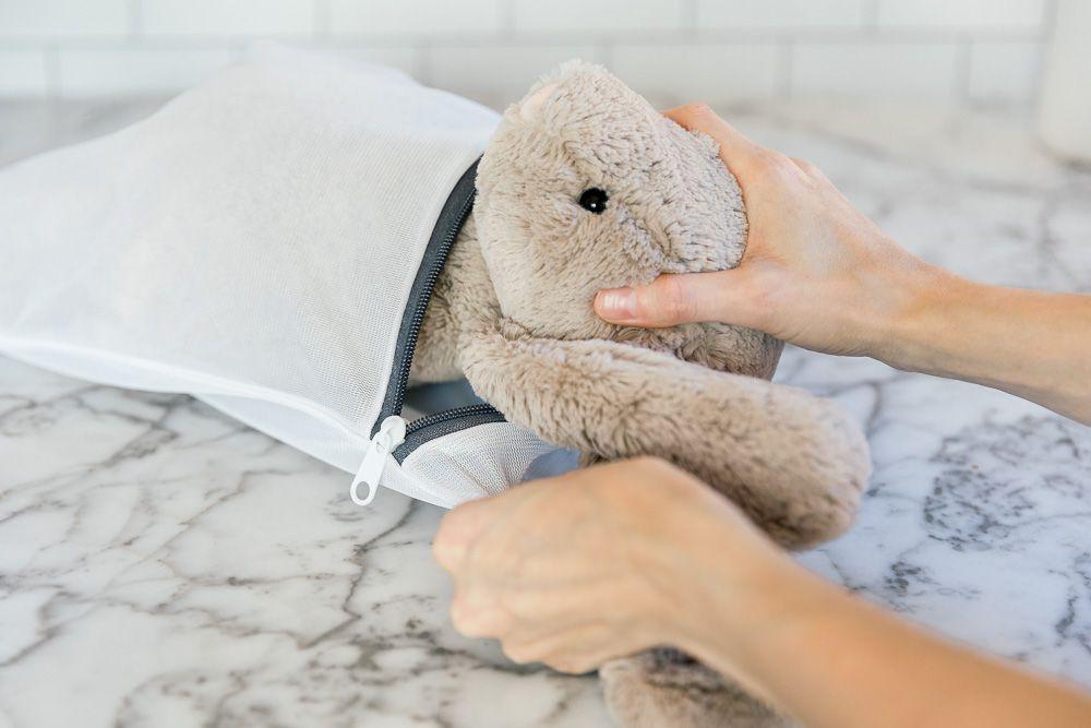 placing the stuffed animal into a mesh laundry bag