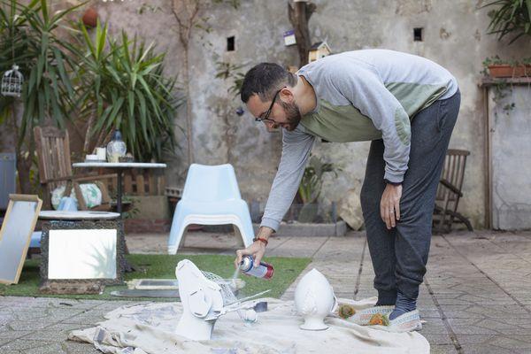 Man spraying decorative objects outside