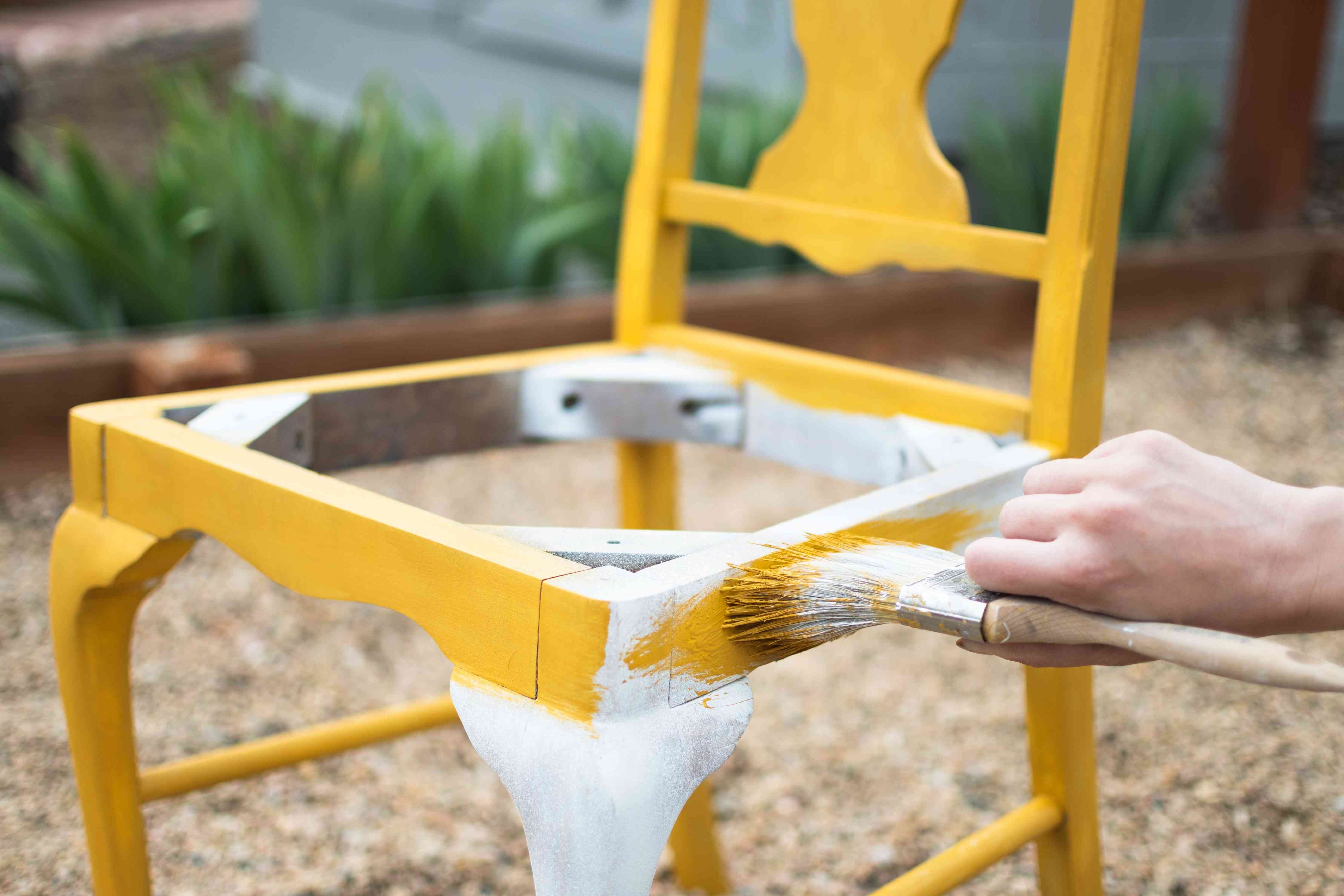 Wooden chair painted with yellow paint over white primer paint with paint brush