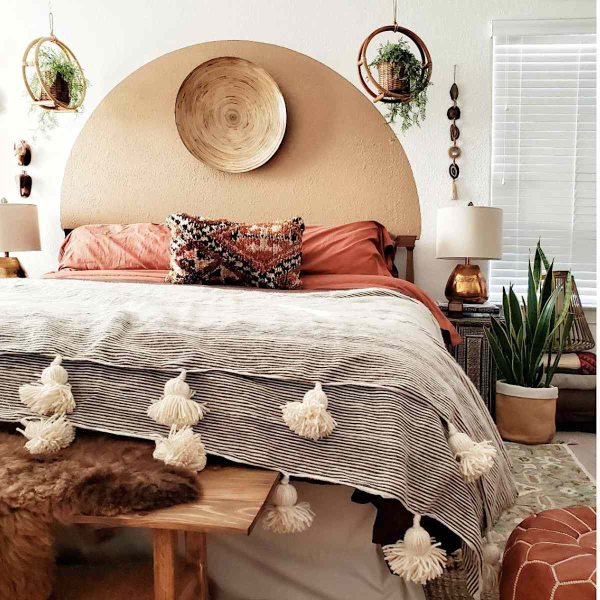 boho style bedroom with warm red, decorated with plants, a painted tan half circle mural over headboard