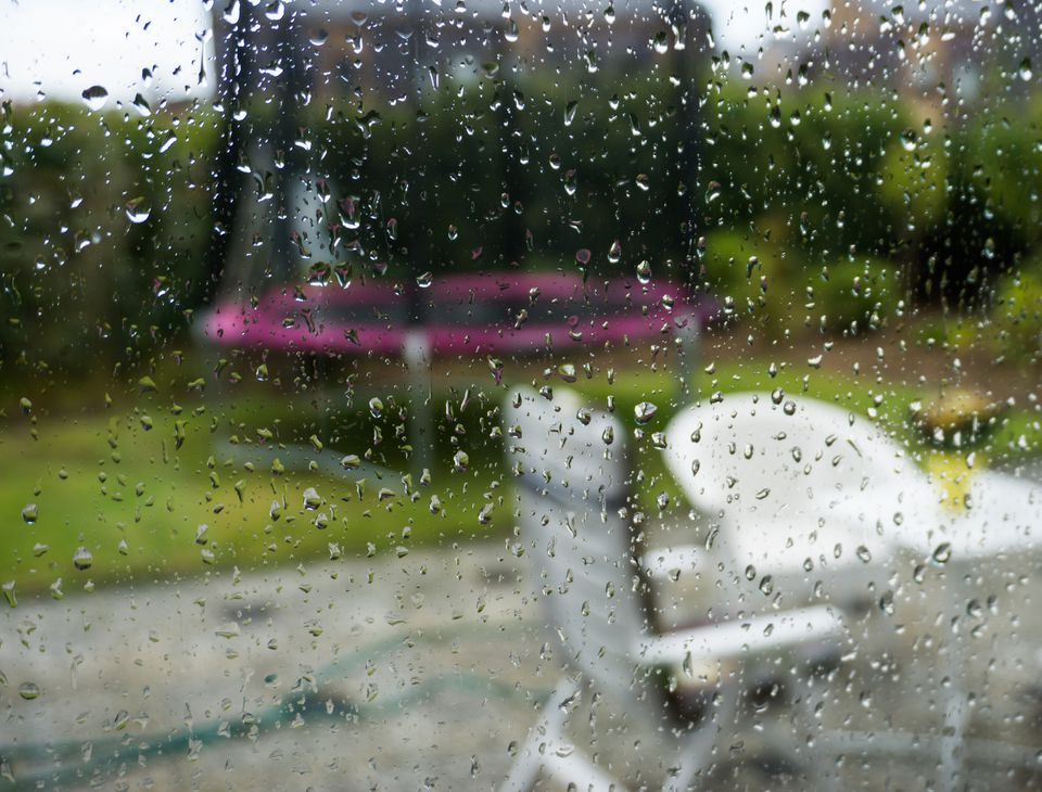 View through a window of a patio with chairs and table getting rained on