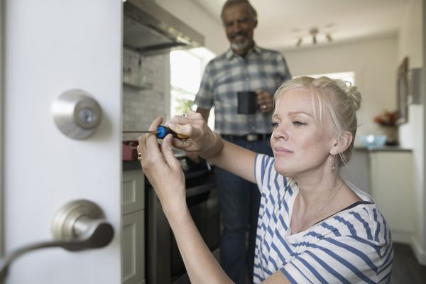Senior father watching daughter fixing door