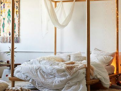 Floral comforter adorning a four-poster bed in a bohemian bedroom.