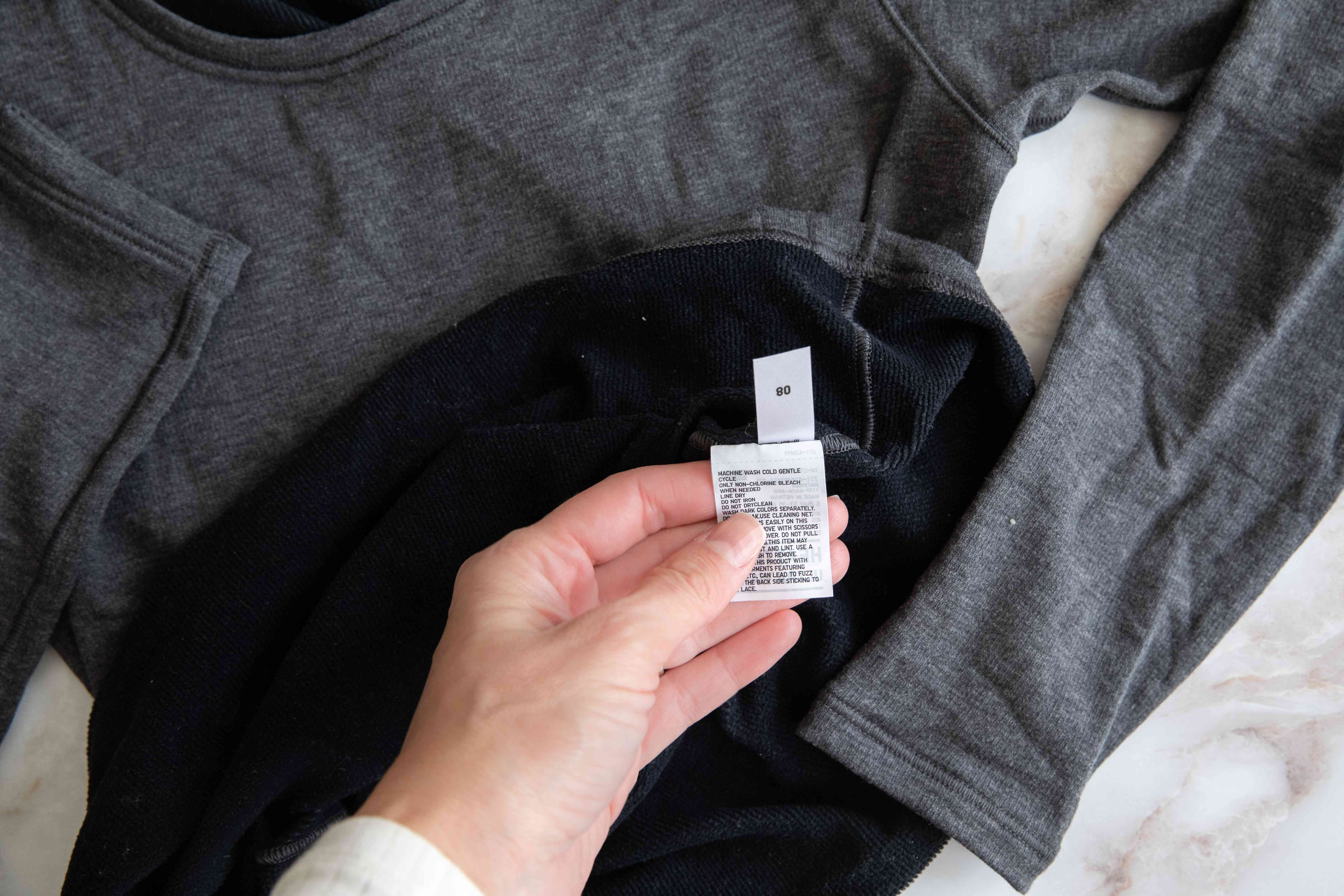 Care labels on gray long sleeved shirt being shown