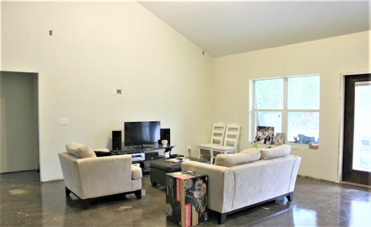 Sala de estar con paredes en blanco y techo abovedado con sillas blancas y sillón de dos plazas antes del cambio de imagen
