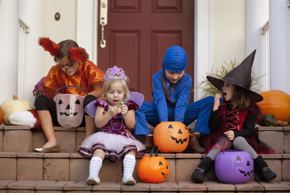 A group of children in Halloween costumes sitting on a front porch.