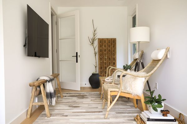 Small room with natural decor items, wicker chairs and tv screen on opposite wall