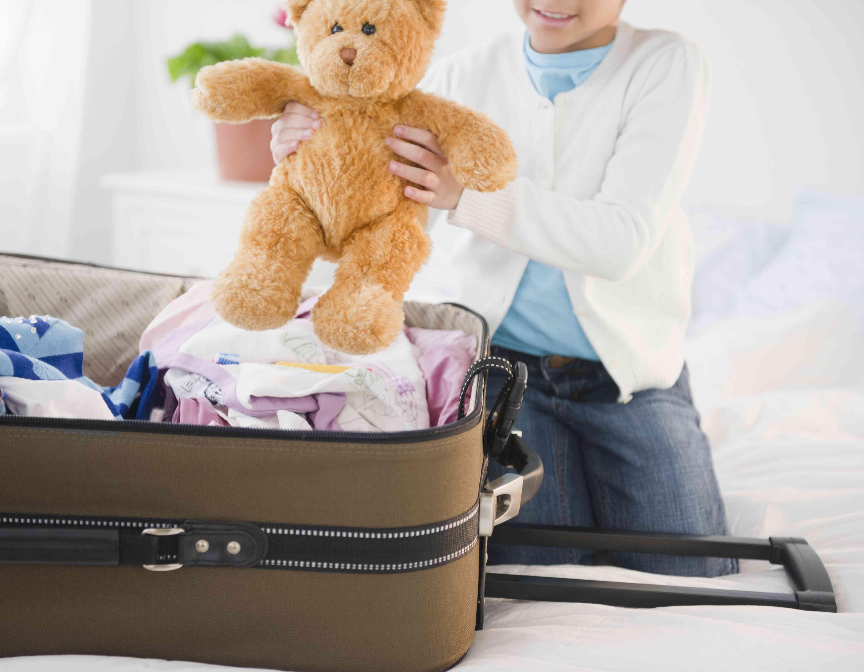 Niña afroamericana que pone el oso de peluche en la maleta