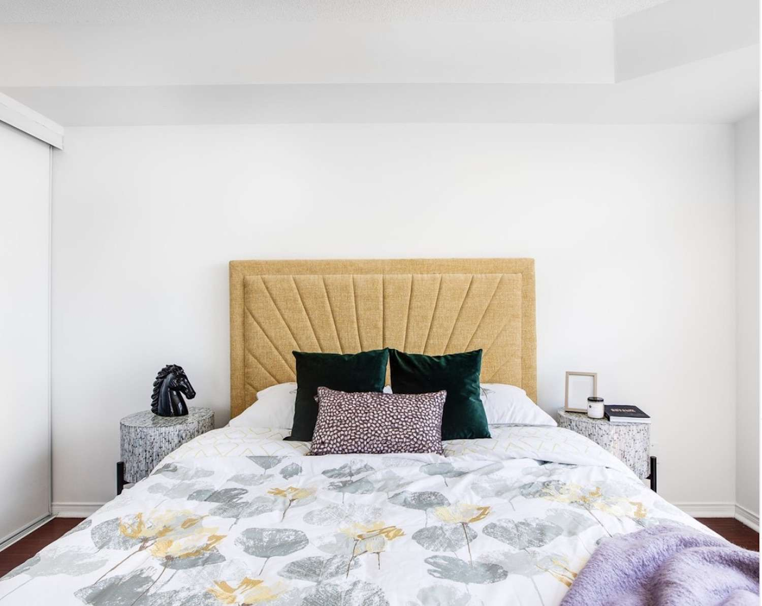 bedrom with yellow and purple color scheme, green accent pillows and white walls,