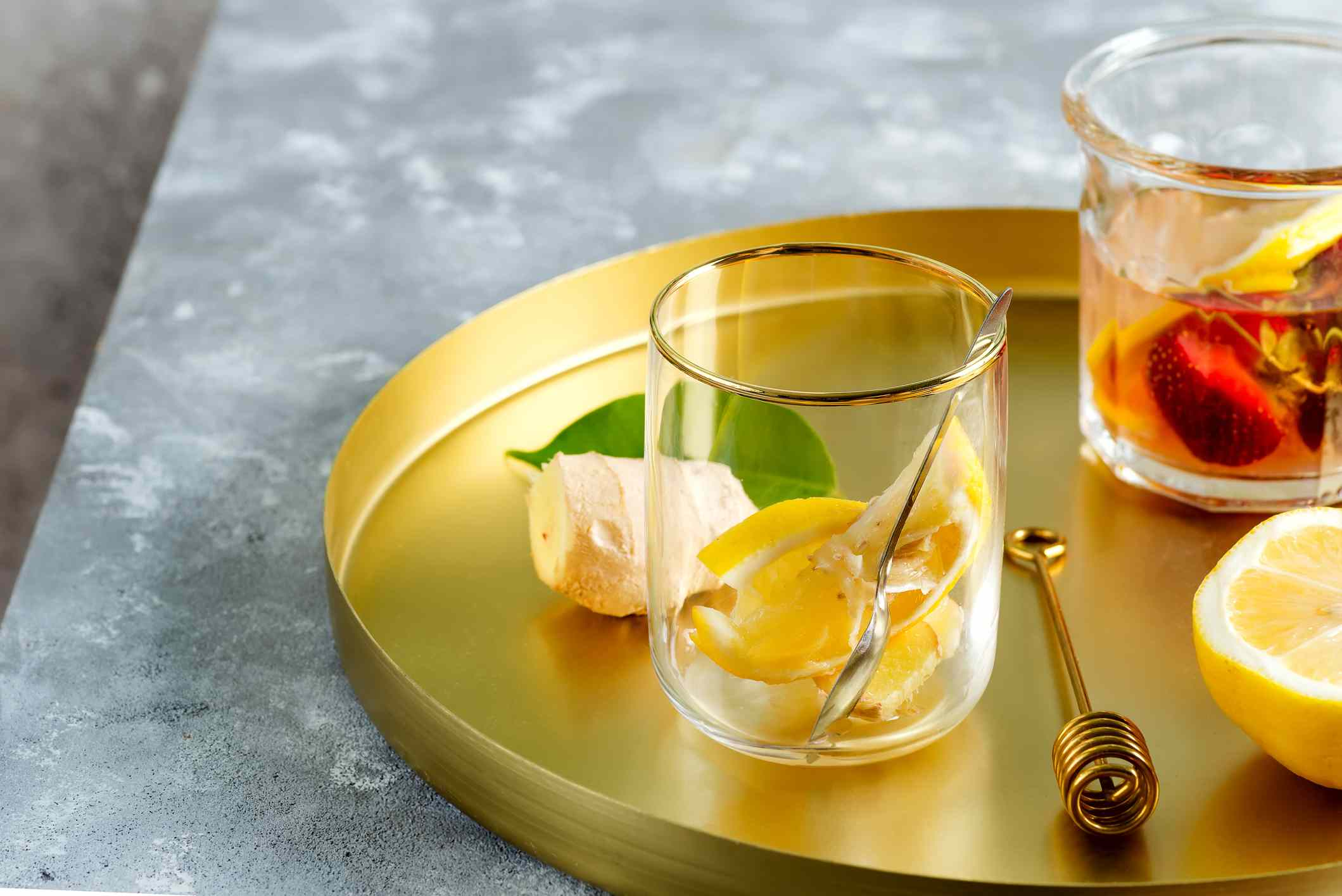 Glasses with lemon in them on a gold serving tray.