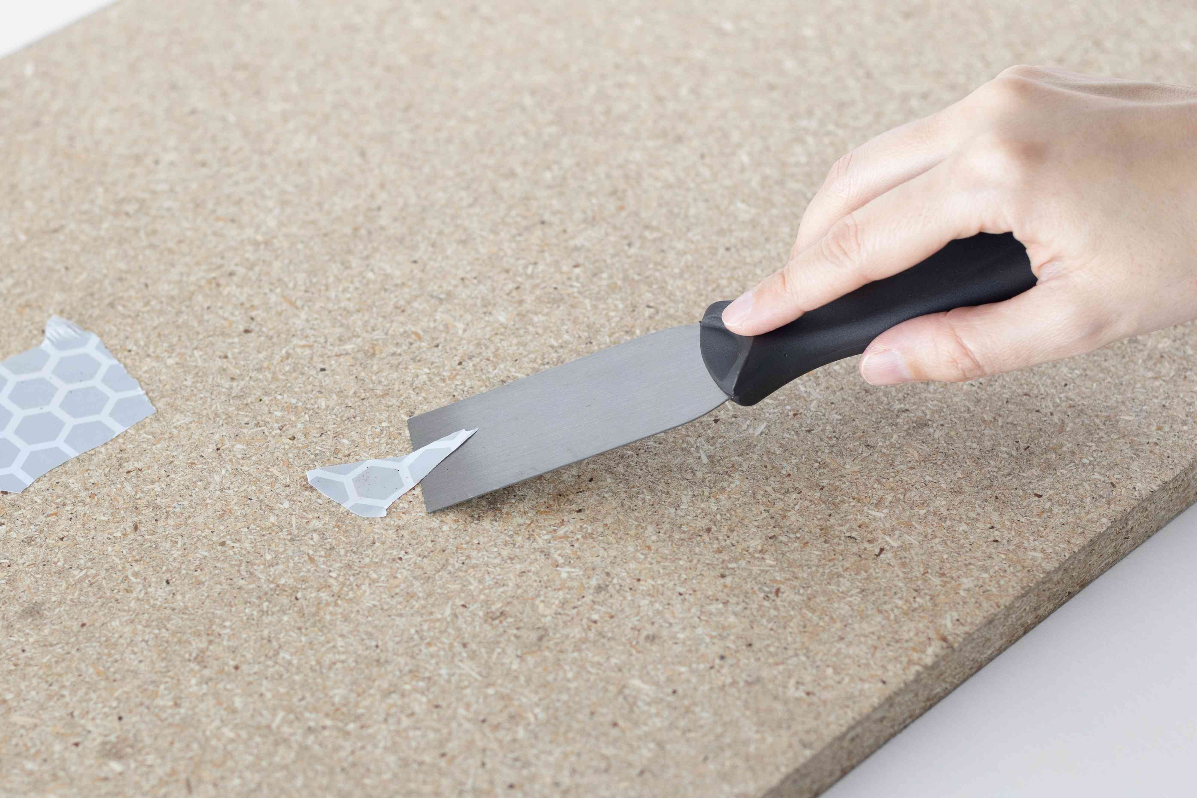 using the putty knife to scrape off any leftover bits of shelf liner