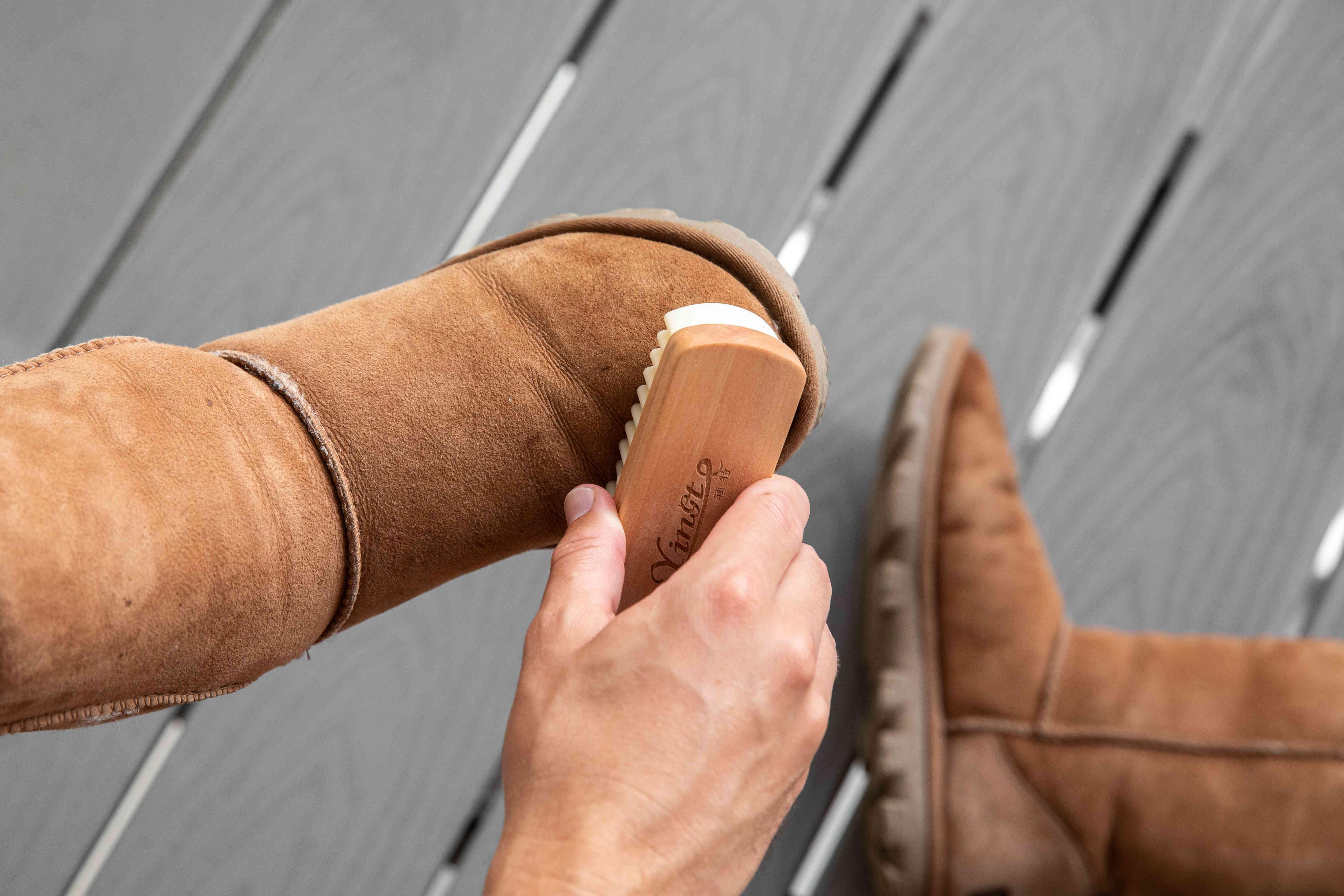 Someone brushing brown Ugg boots