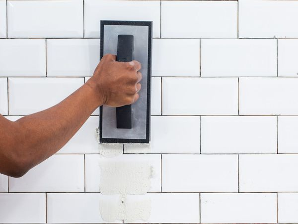Person adding grout to tile wall