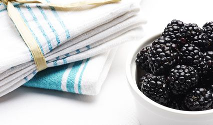 Stack of blue and white tea towels next to bowl of blackberries on white background