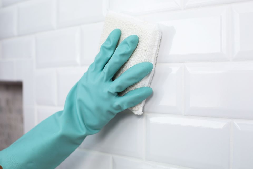 Grout haze cleaned off white tiled wall with white sponge and teal gloves