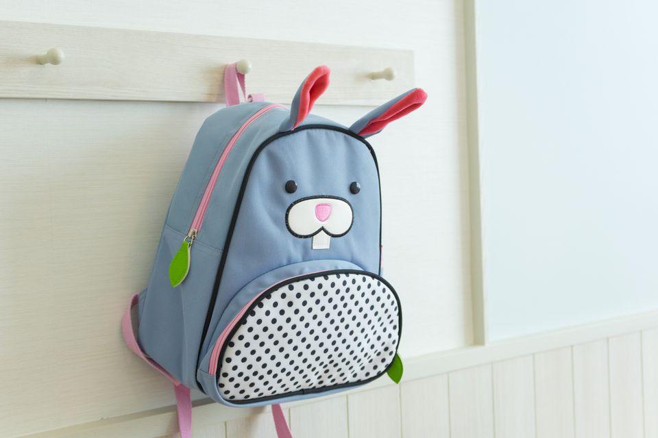 school rucksack hanging on the wall in kid bedroom.