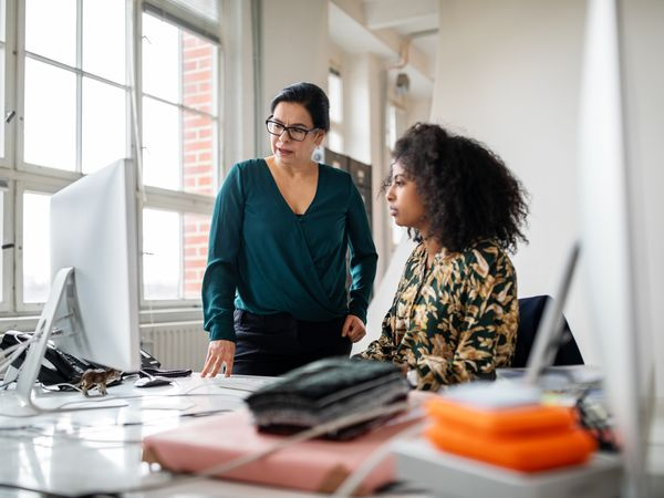Senior businesswoman helping young colleague in office