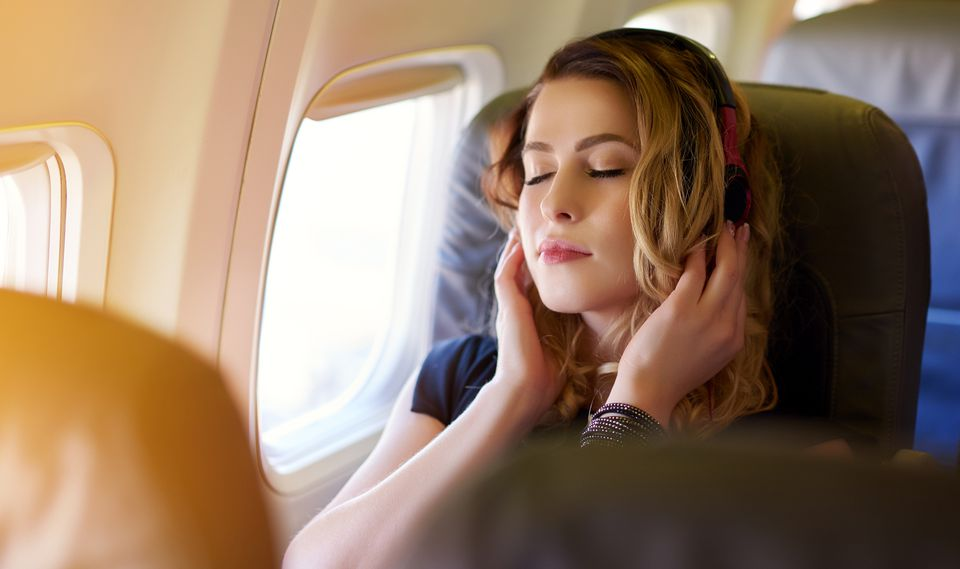 A woman listening to music in an airplane