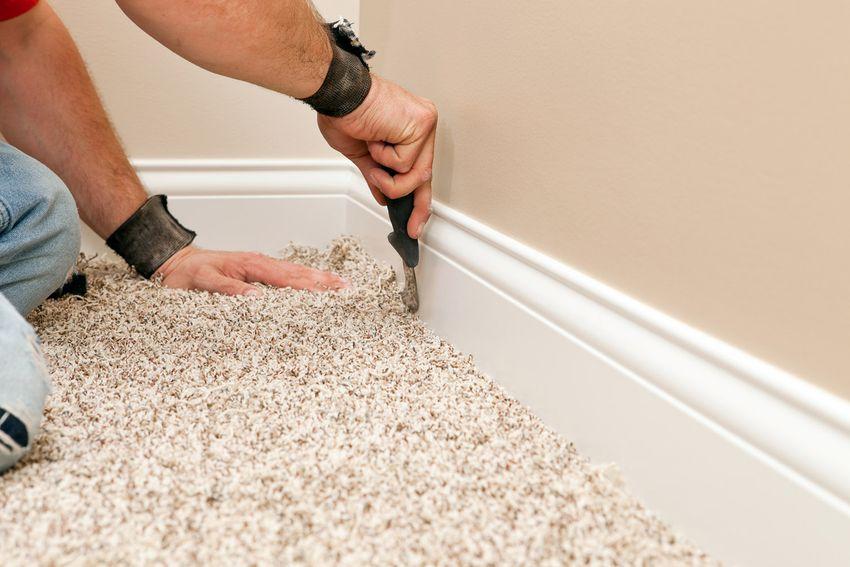 Installer Using Carpet Knife to Tuck New Floor