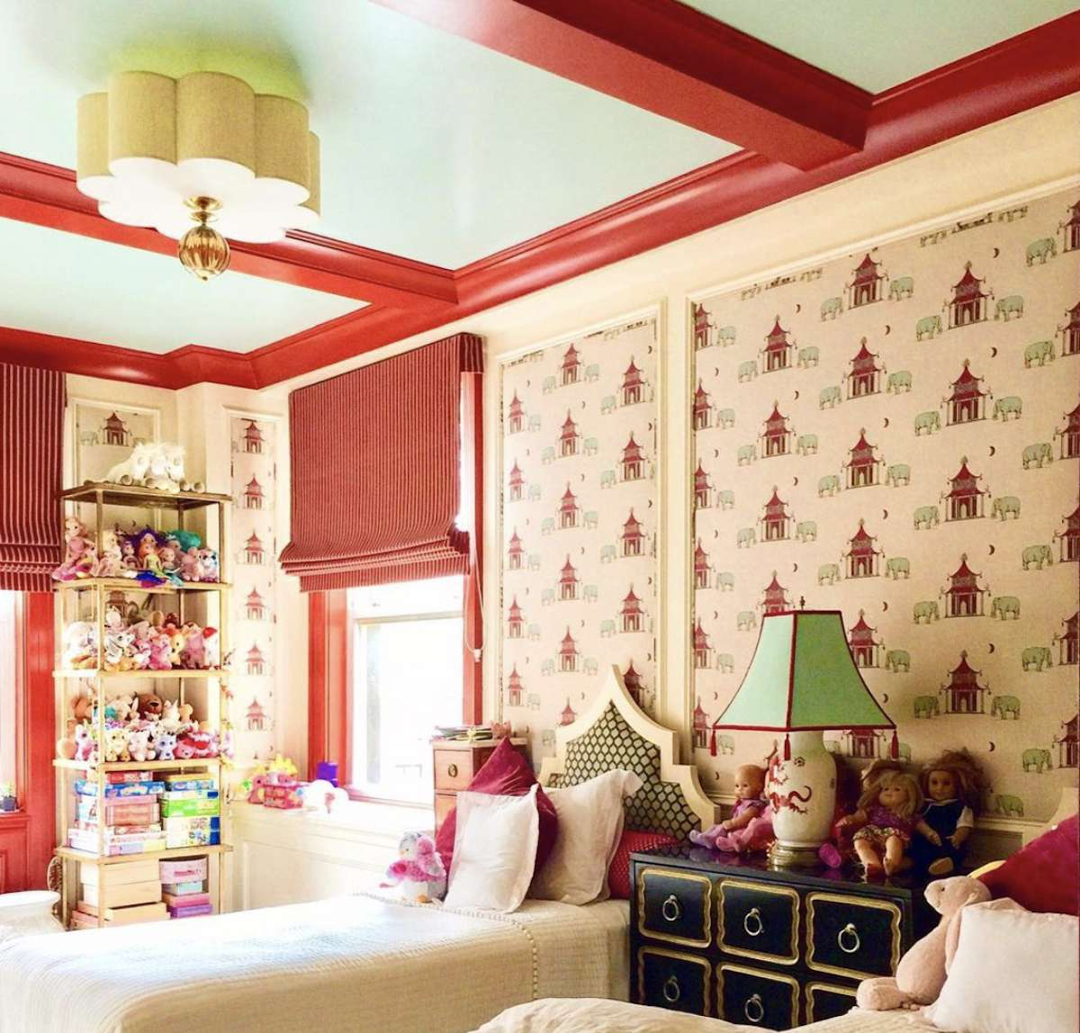 child's bedroom with red houses on wallpaper, exposed red beams on ceiling