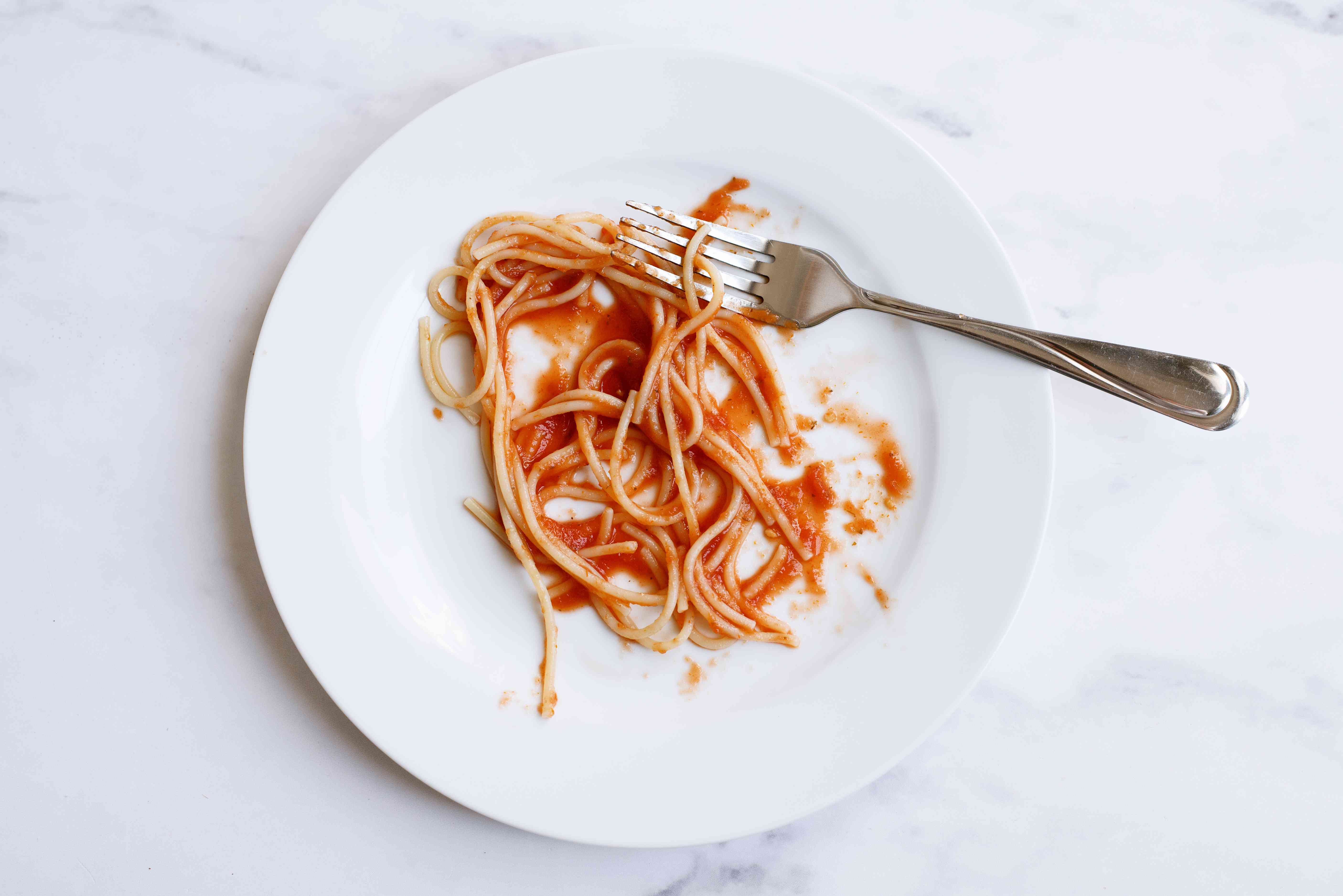 White plate with leftover pasta noodles and sauce with fork on top