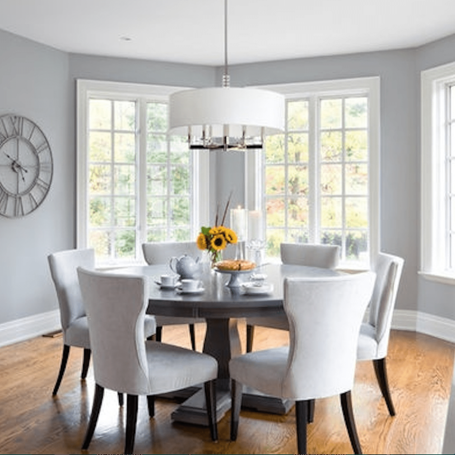 Dining room with white fabric chairs, table, hanging light, and gray walls.