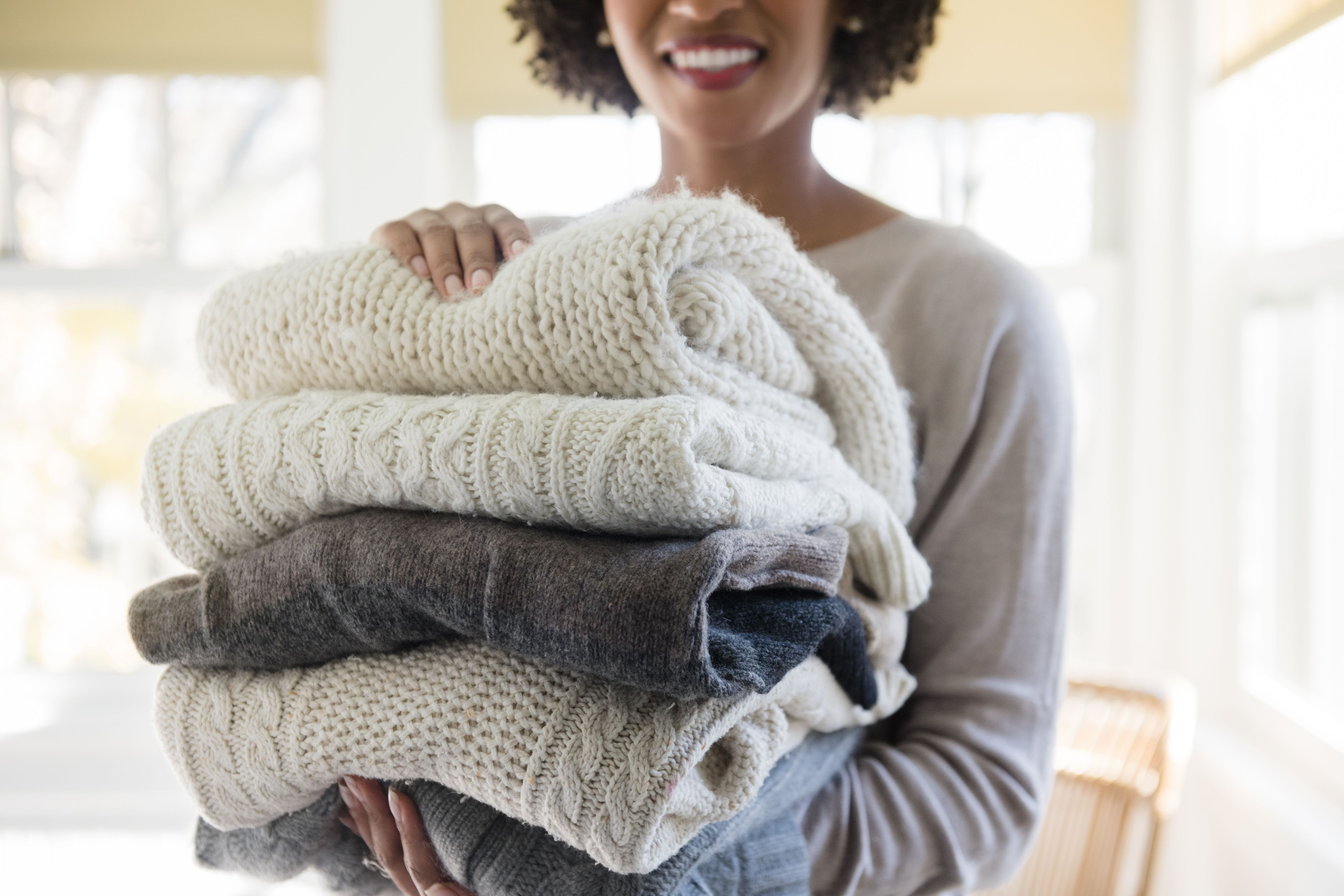 Woman holding a stack of folded sweaters.