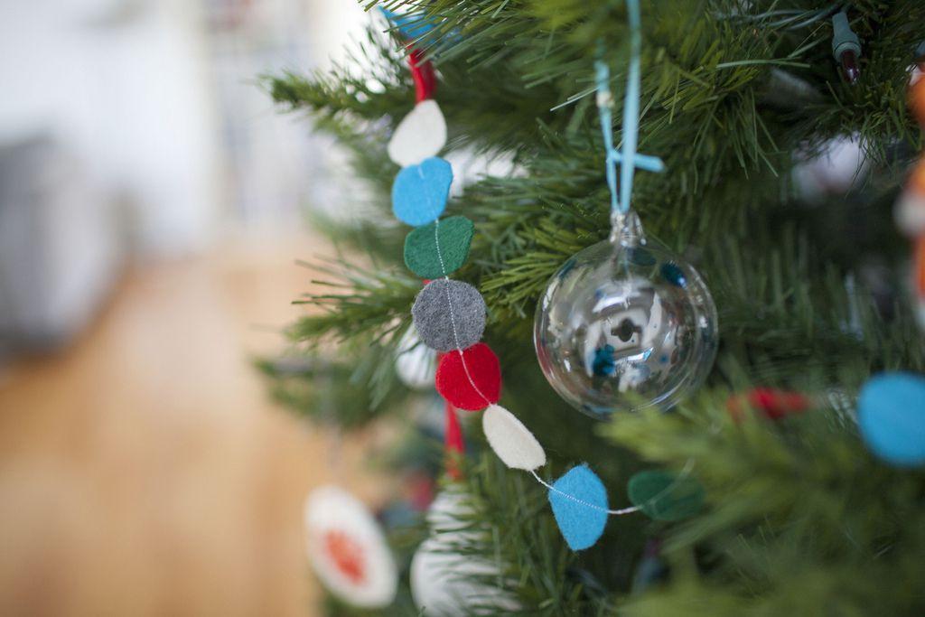 Un árbol de Navidad flocado completo cerca de una mesa auxiliar y una lámpara