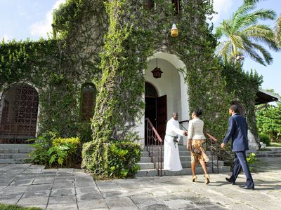 Priest greeting Sunday church worshippers at Ivy covered church in St. Ann's Bay, Jamaica.