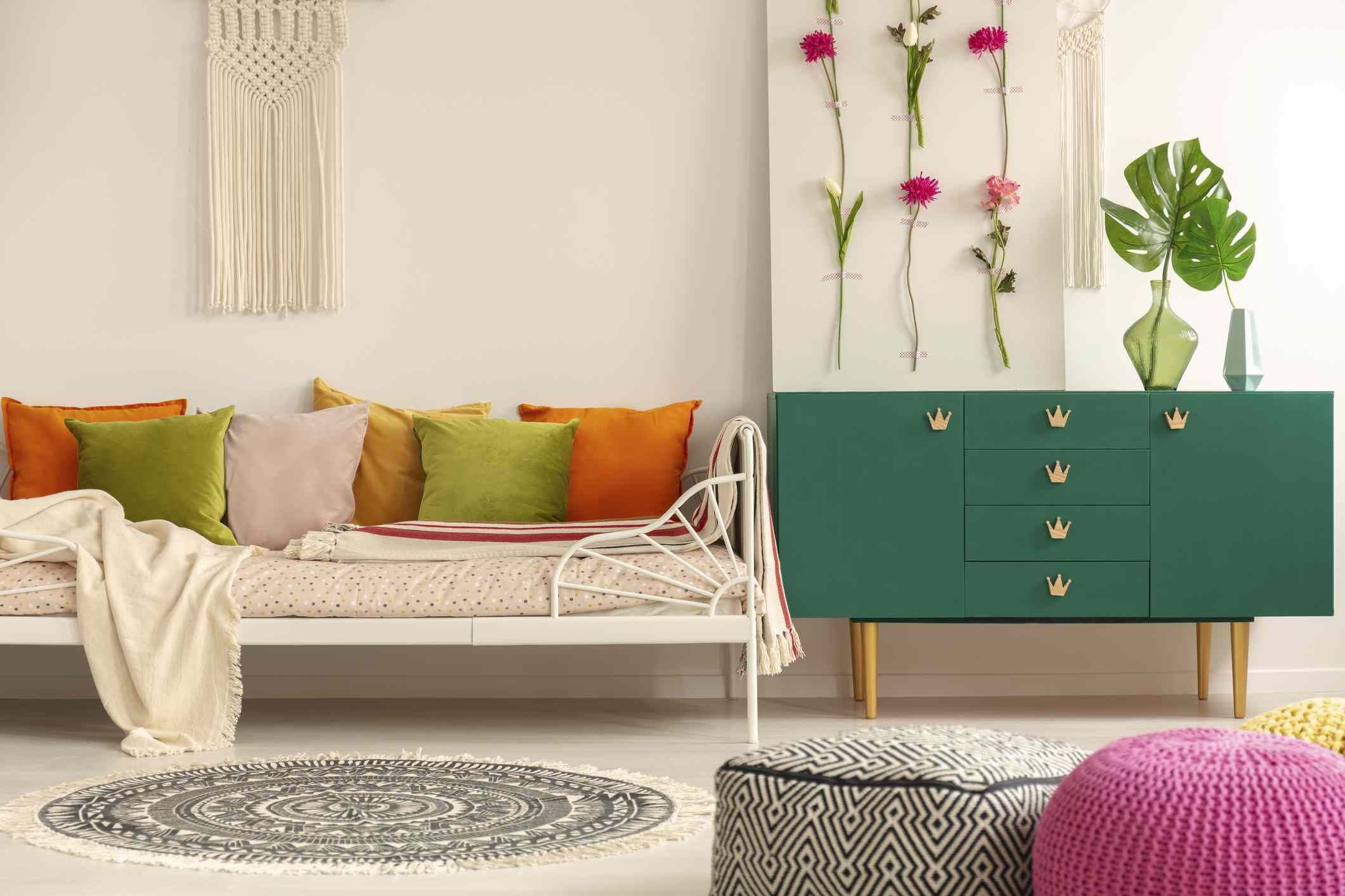 Handmade flower board on green wooden cabinet with leaf in glass vase next to comfortable sofa with olive green, pastel pink, yellow and orange pillows