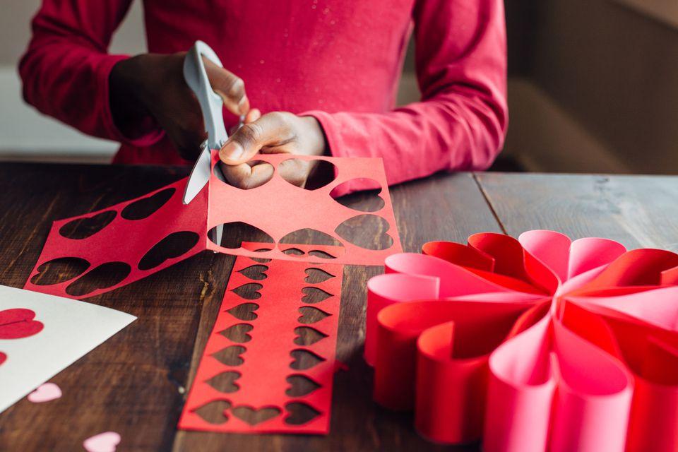 una niña cortando corazones de papel
