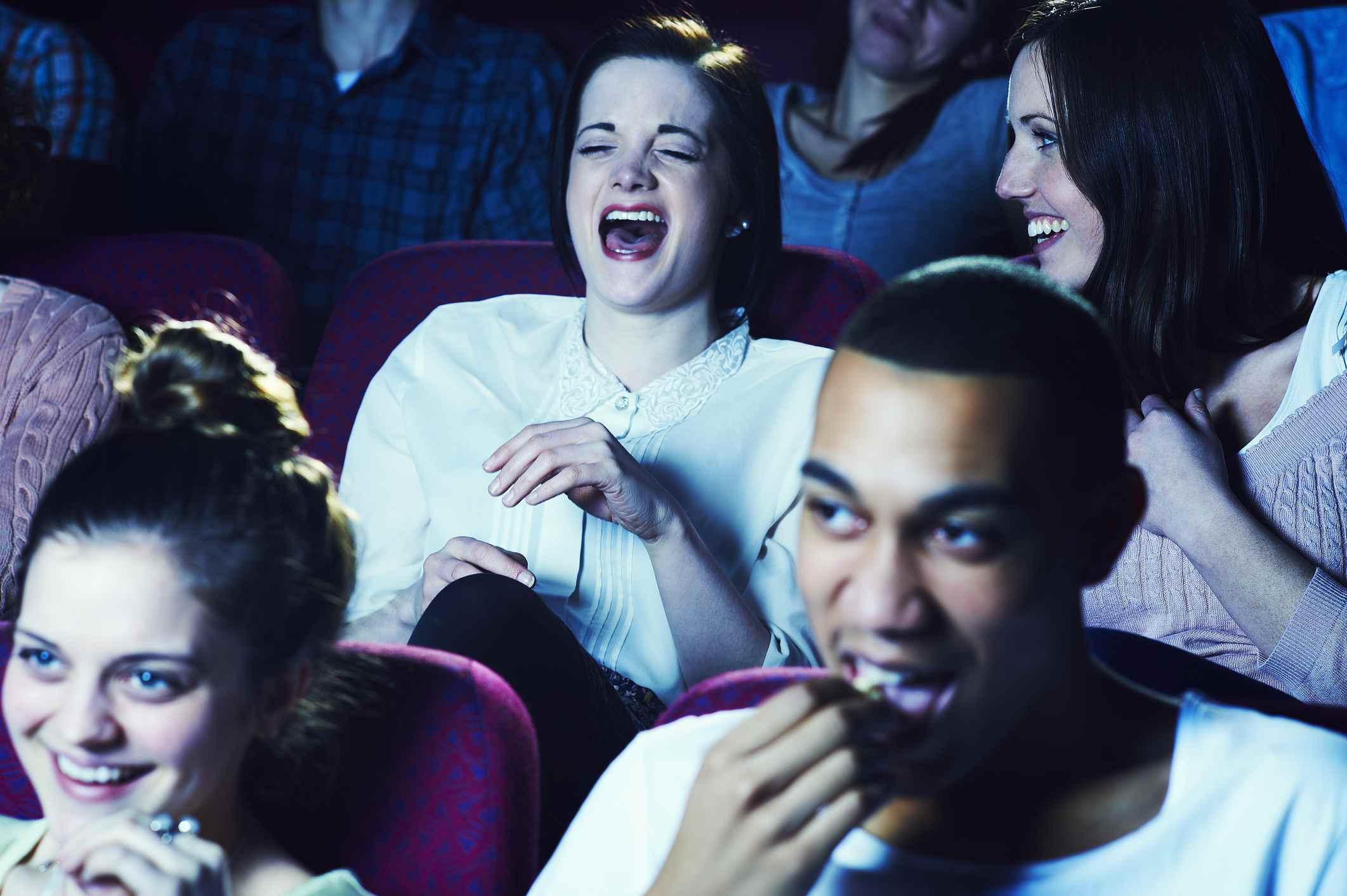 Women laughing in a movie theater.