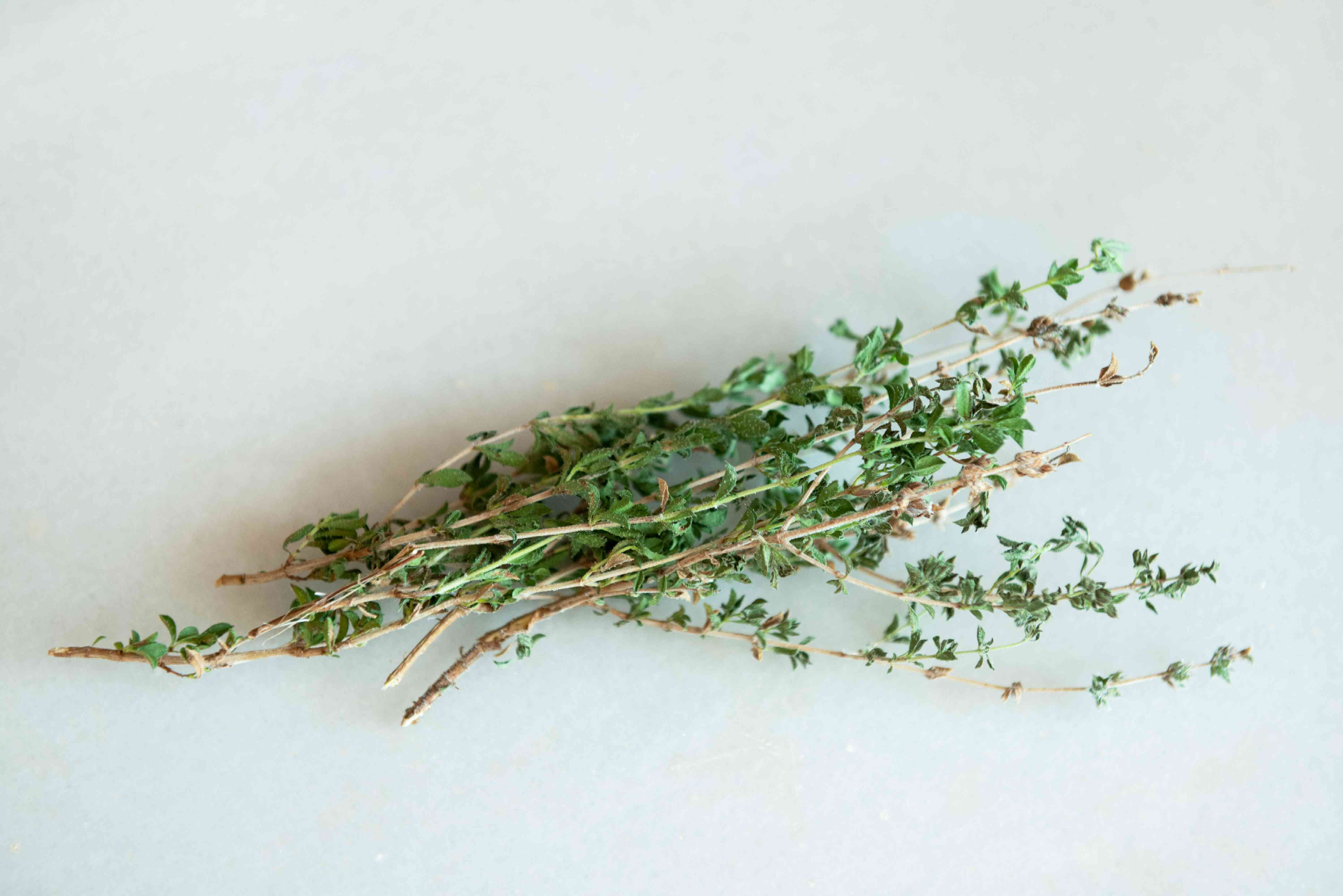 Summer savory herb stems lying in a stack on white surface