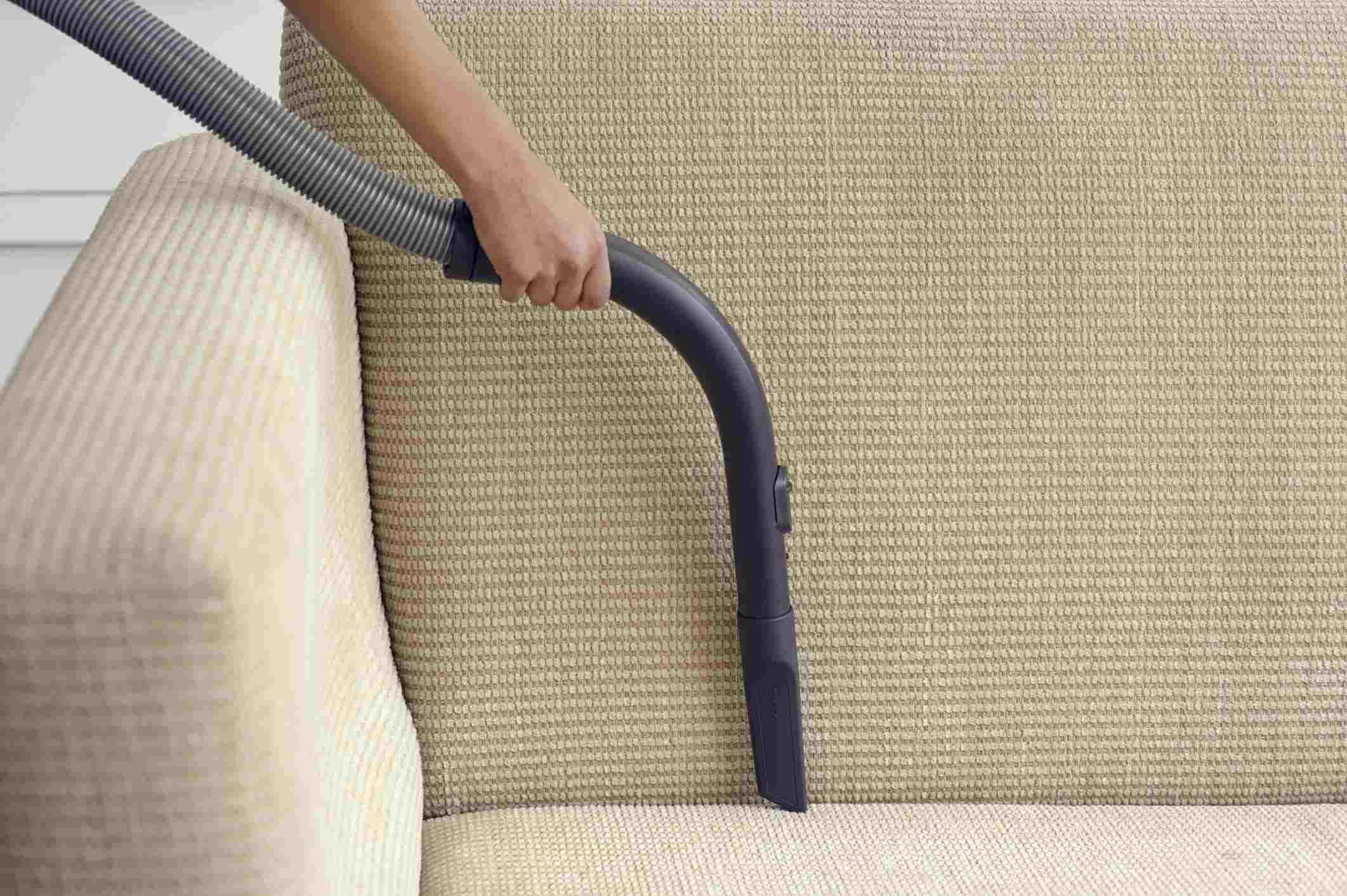 Woman removing dust from sofa edge using vacuum cleaner