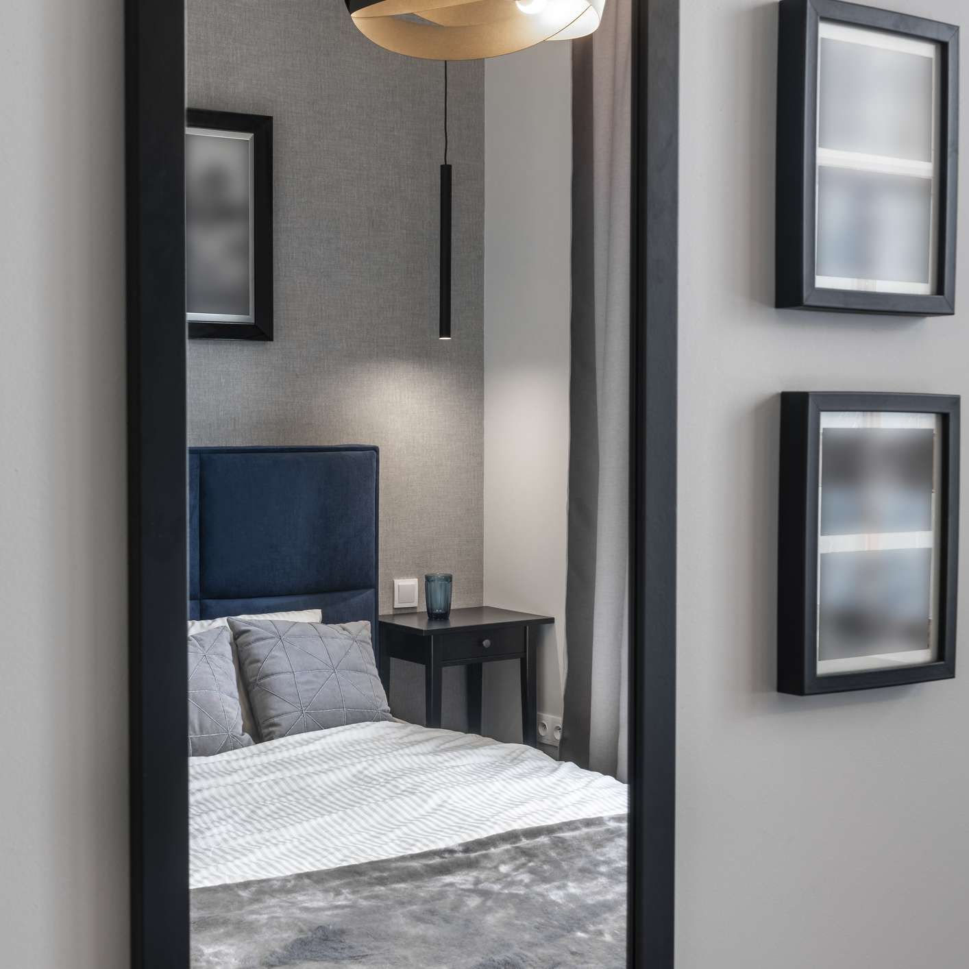 Modern bedroom in gray finishing with blue bed and mirror