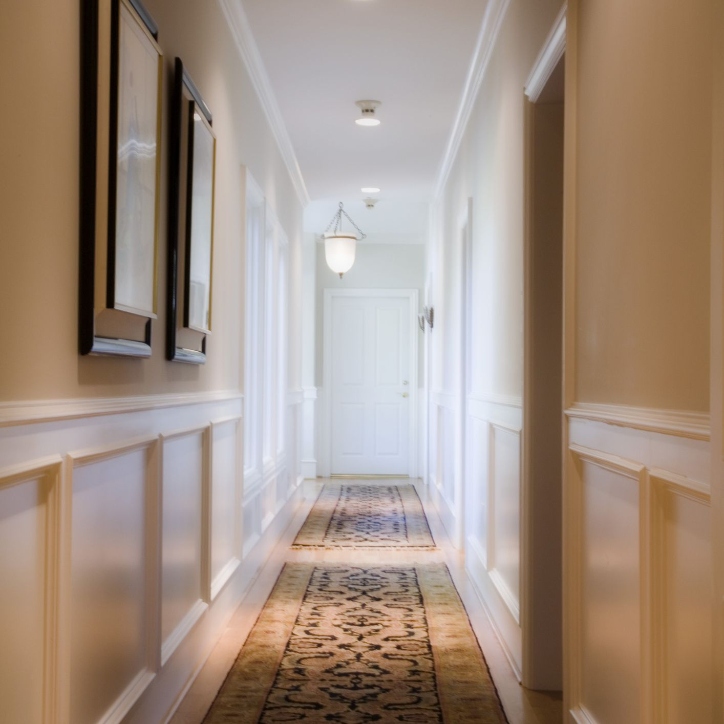 a long hallway with art and runners on the floor with lighting