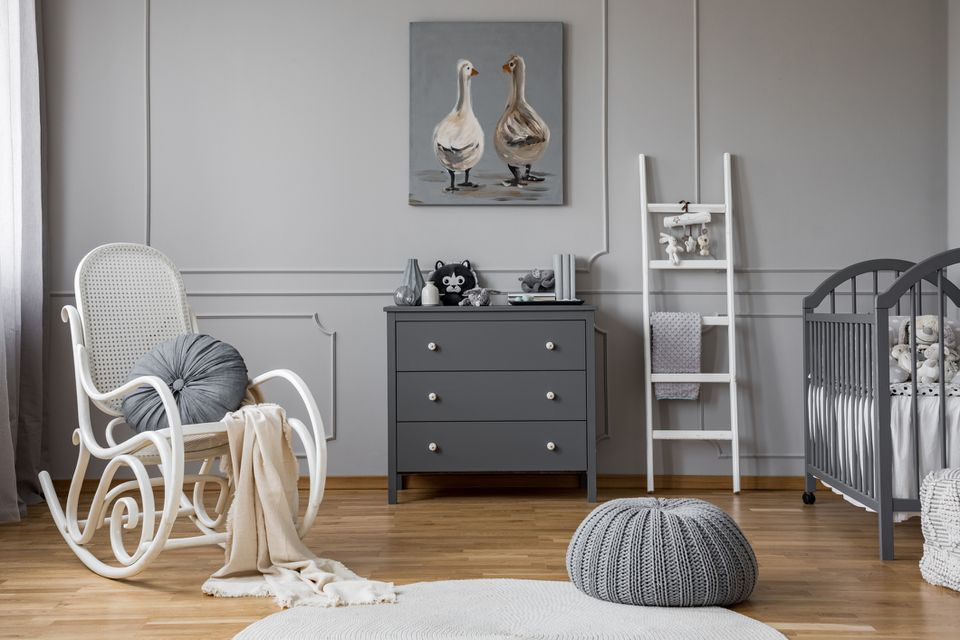 Pouf and rocking chair in grey baby's bedroom interior with ladder next to cabinet. Real photo